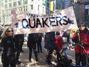 Quakers at a climate justice march, holding up a banner that reads 'Vancouver Quakers'