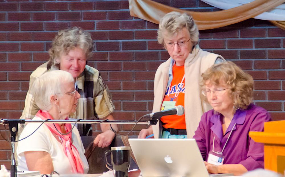 Carol, Susan, Elaine and Marilyn craft a minute at Yearly Meeting